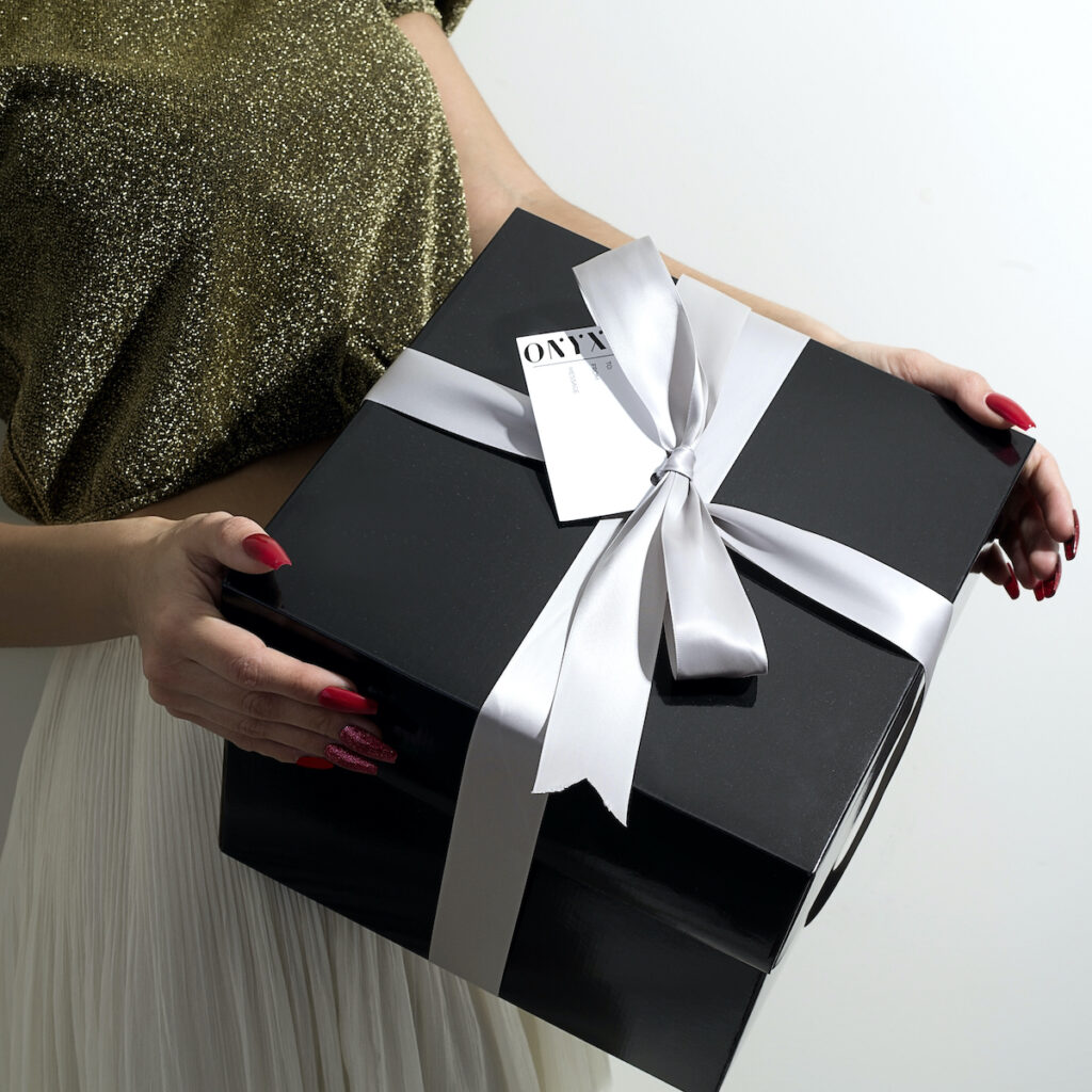 Woman holding a gift box from Onyx Nails